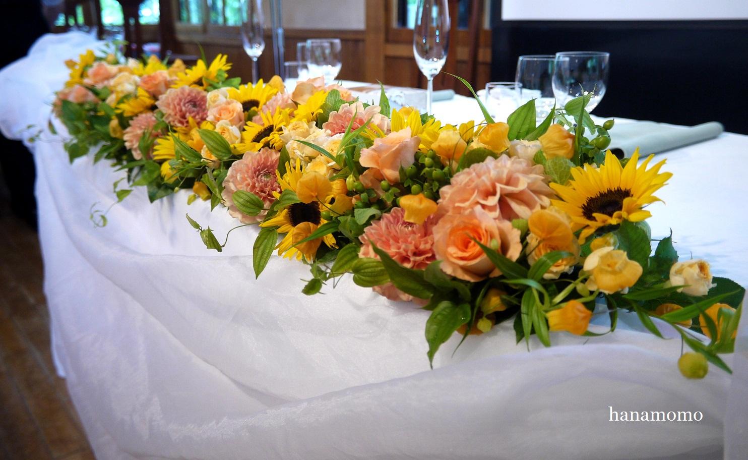 本日のすいぎょく様での結婚式の会場装花はヒマワリ・ダリア・バラ・サンダーソニア等元気いっぱいビタミンカラーのメインテーブル装花